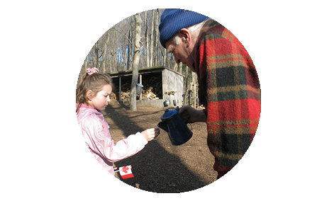 A man pouring maple syrup into a cup held by a child