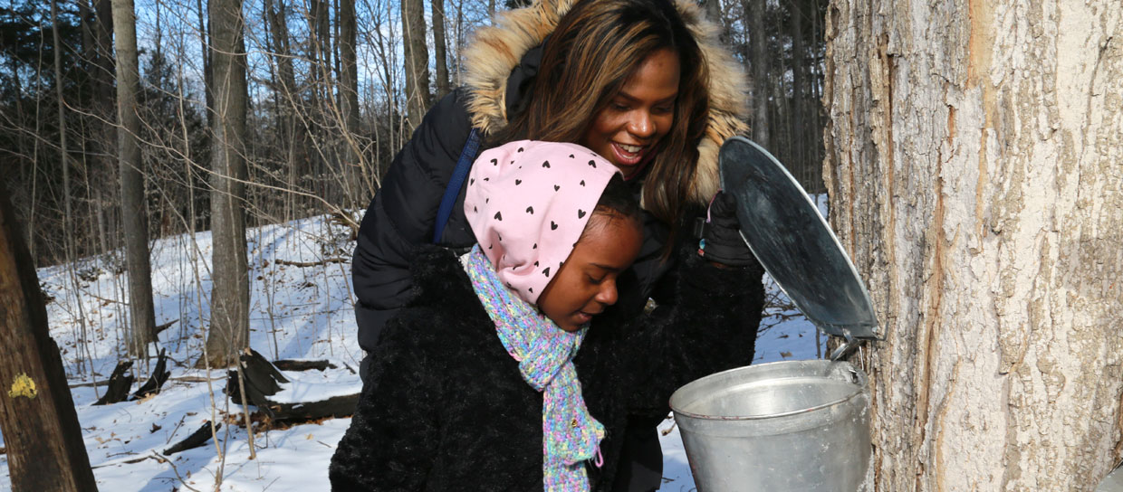 A mother and child looking in a maple sap bucket in the forest